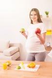 美丽的孕妇在厨房里烹调 图库摄影