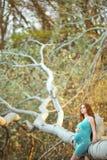 美丽的孕妇在庭院里 免版税库存照片