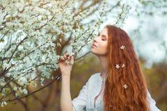 美丽的孕妇在开花的庭院里 免版税图库摄影