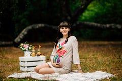 美丽的孕妇在秋天公园握腹部 免版税库存图片