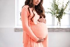 美丽的孕妇拿着腹部特写镜头 库存照片