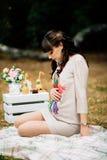 美丽的孕妇是和看起来可爱坐腹部 免版税库存图片