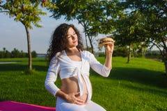 美丽的孕妇用一个汉堡在公园 库存照片