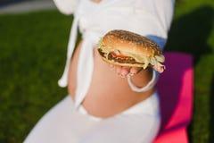 美丽的孕妇用一个汉堡在公园 库存图片