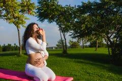 美丽的孕妇用一个苹果在公园 库存照片