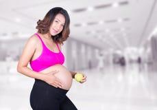 美丽的孕妇用绿色苹果在医院 库存图片