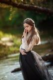 美丽的孤独的女孩敏感艺术画象摆在户外和看您的森林俏丽的妇女的 库存照片