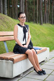 美丽的学校女孩或学生坐长凳在公园 免版税库存照片