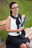 美丽的学校女孩或学生画象坐长凳  免版税库存照片