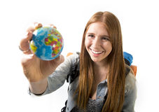 美丽的学生女孩在她的手上的拿着一点世界地球选择在旅行旅游业概念的假日目的地 免版税库存照片