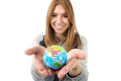 美丽的学生女孩在她的手上的拿着一点世界地球选择在旅行旅游业概念的假日目的地 图库摄影