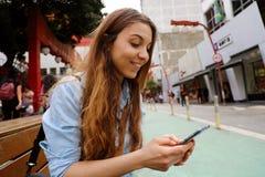 美丽的学生女孩坐街道与手机的长凳传讯在圣保罗市,巴西 库存图片