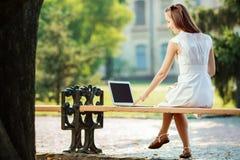 美丽的学生妇女使用一台膝上型计算机并且坐长凳 免版税库存照片