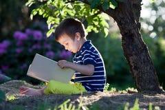 美丽的孩子男孩,读一本书在庭院里,坐在t旁边 免版税库存照片
