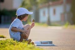 美丽的孩子男孩,读书在街道,坐下wi 库存图片