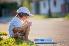 美丽的孩子男孩,读书在街道,坐下wi 库存照片