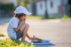 美丽的孩子男孩,读书在街道,坐下wi 图库摄影