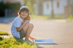 美丽的孩子男孩,读书在街道,坐下wi 免版税库存图片
