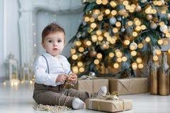 美丽的宝贝在圣诞树和礼物盒附近坐 图库摄影