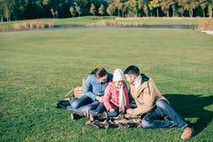 美丽的家庭坐绿色草甸 免版税库存图片
