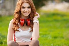 美丽的对妇女的耳机听的音乐 图库摄影