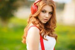 美丽的对妇女的耳机听的音乐 免版税库存图片
