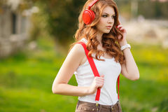 美丽的对妇女的耳机听的音乐 免版税库存照片