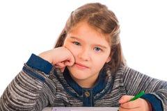 美丽的小女孩乏味做家庭作业 免版税库存照片
