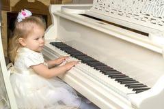 美丽的小女孩在一架白色大平台钢琴使用 免版税库存照片