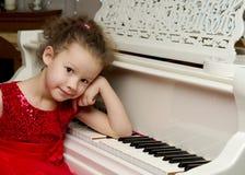 美丽的小女孩在一架白色大平台钢琴使用 图库摄影