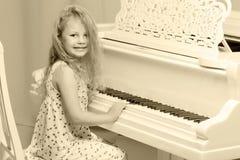 美丽的小女孩在一架白色大平台钢琴使用 库存图片