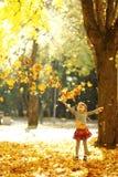 美丽的小女孩在使用本质上的秋天公园 图库摄影