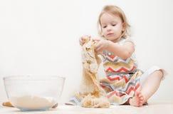 美丽的小女孩在厨房里学会烹调一顿膳食 免版税库存图片