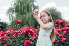 美丽的小女孩在开花的庭院做一个姿态 免版税库存照片