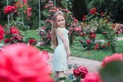 美丽的小女孩在开花的庭院里 免版税库存图片