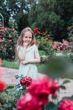 美丽的小女孩在开花的庭院里 库存照片