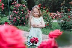 美丽的小女孩在开花的庭院里 库存图片