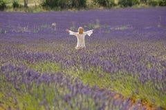 美丽的小女孩在淡紫色的领域跑 免版税图库摄影