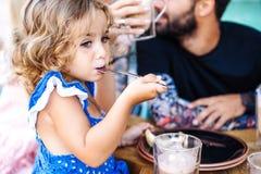美丽的小女孩坐吃点心 免版税库存图片