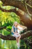 美丽的小女孩坐日志在河下 库存图片