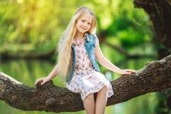 美丽的小女孩坐日志在河下 免版税库存图片