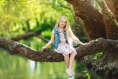 美丽的小女孩坐日志在河下 免版税库存照片