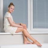 美丽的小女孩坐白色楼梯 库存图片