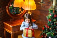 美丽的小女孩打开坐在圣诞树附近的礼物 免版税库存照片