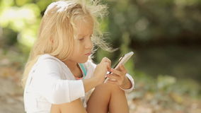 美丽的小女孩拍在电话的照片 股票录像