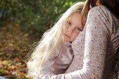 美丽的小女孩拥抱她的母亲 免版税库存图片