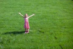 美丽的小女孩涂了站立她的胳膊  免版税库存图片