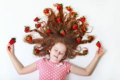 美丽的小女孩用在她的头发的草莓 免版税库存照片
