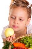 美丽的小女孩用苹果和蔬菜 免版税库存图片