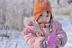 美丽的小女孩画象在冬天森林里 免版税库存图片
